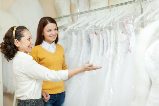 Shop assistant  helps bride in choosing  dress